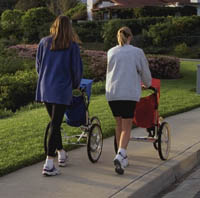 Two mothers walking with jogging strollers