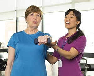 Rehab therapist working with senior woman doing exercises with hand weights.