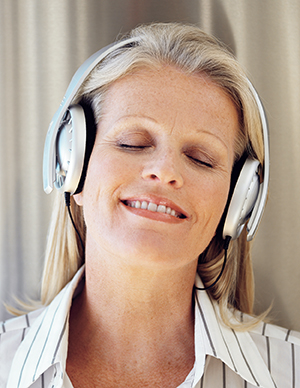 Smiling woman with eyes closed wearing headphones.