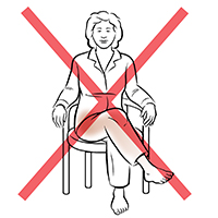 Front view of woman sitting in chair with legs crossed. Red X indicates not to do this.