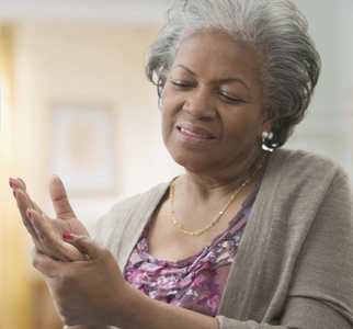 Older woman feeling her hand, in pain