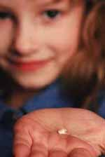 Picture of a young girl holding a tooth