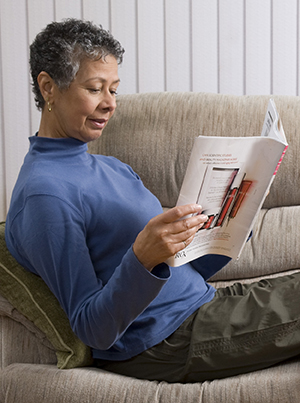 Woman reading magazine on couch with feet elevated.